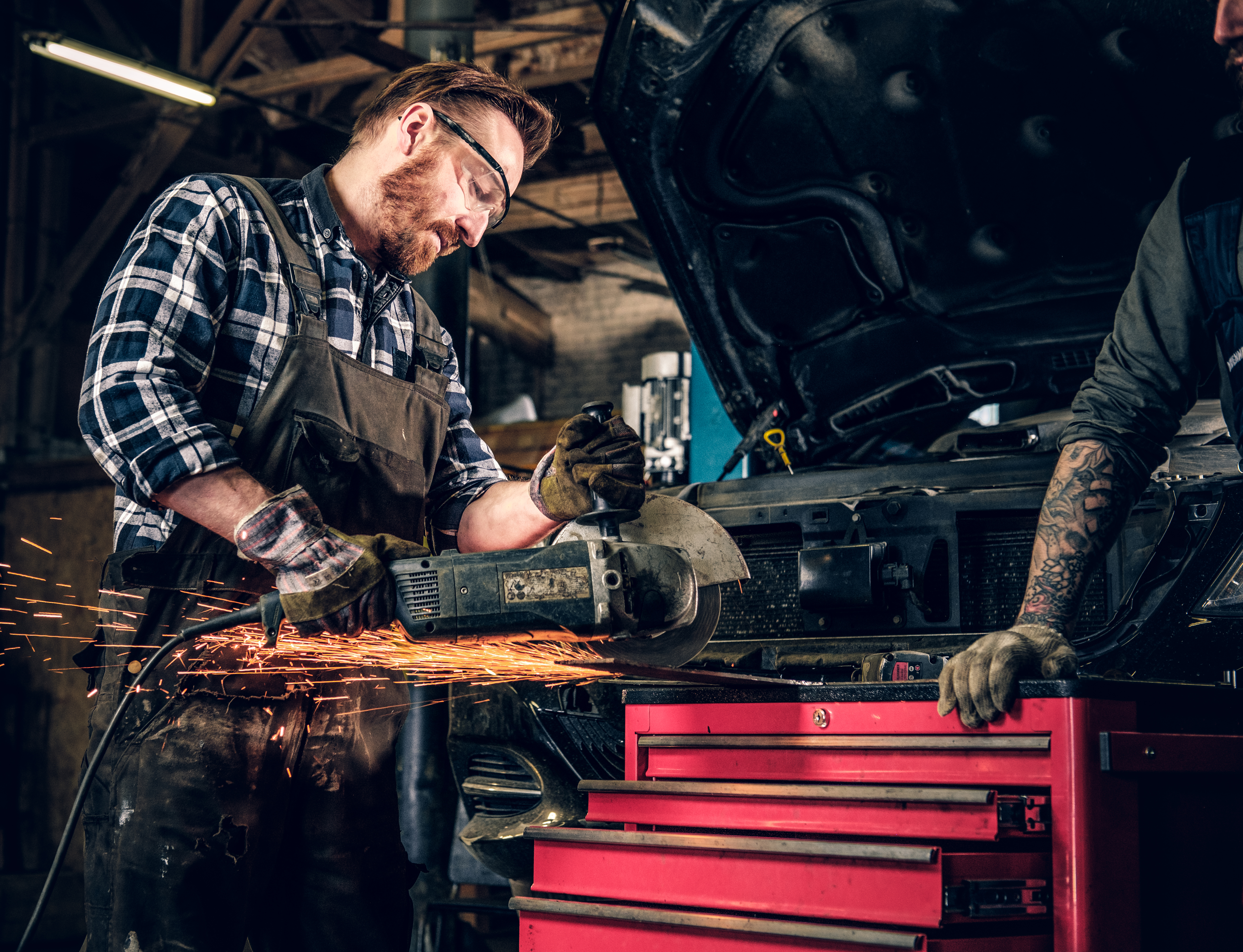 Bearded mechanic cuts steel car part with an angle grinder in a garage.